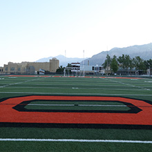 Ogden High School Filed with school building and mountain view in the background.
